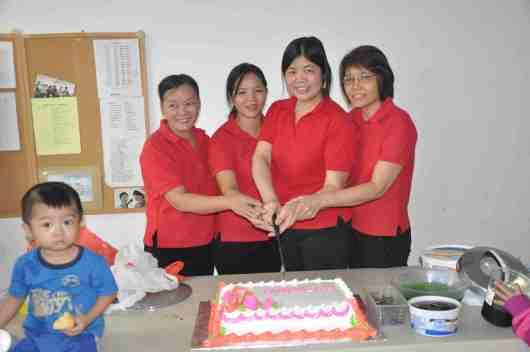 Adult Choral Group cutting celebration cake