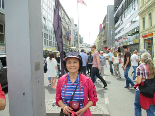 Checkpoint Charlie in background, under US flag. Charlie stands for C i.e. Checkpoint #3.