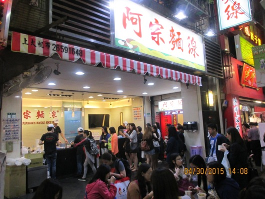 The famous Ah-chung Rice Noodle, where people wait in long lines for a bowl of noodles to eat while standing on the street.