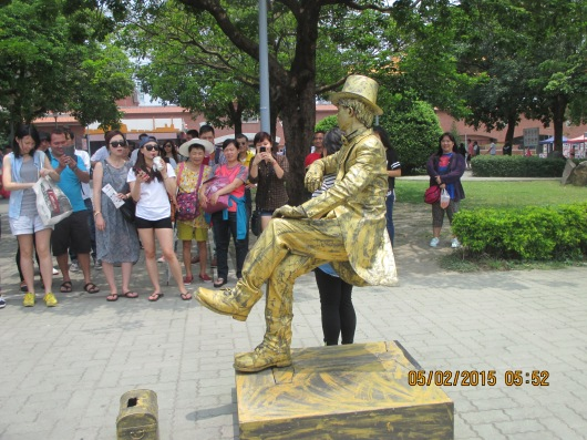 "Street performer ""sitting"" in this posture with no visible means of support. Seat hiding inside his pants?"